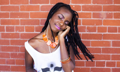 Black woman listening to earbuds near brick wall